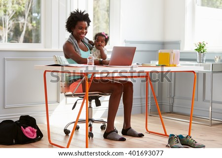 Woman holding child using computer at home after exercising - stock photo