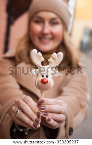Woman holding christmas lollipop deer - stock photo