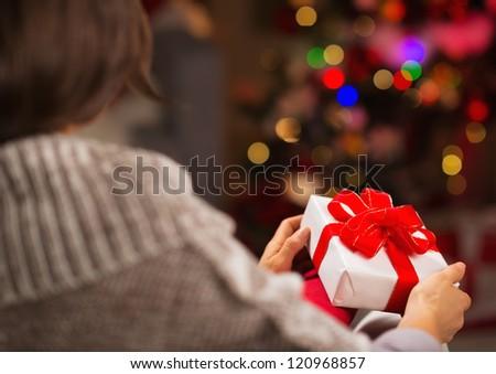 Woman holding Christmas present box. Rear view - stock photo