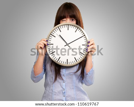Woman Holding Clock Winking Isolated On Grey Background - stock photo