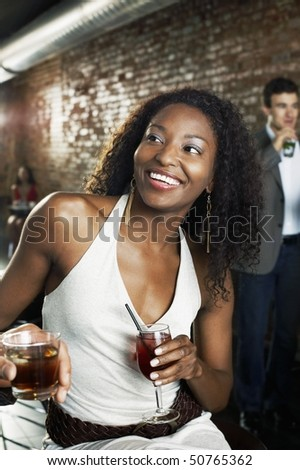 Woman holding cocktail, sitting in bar - stock photo