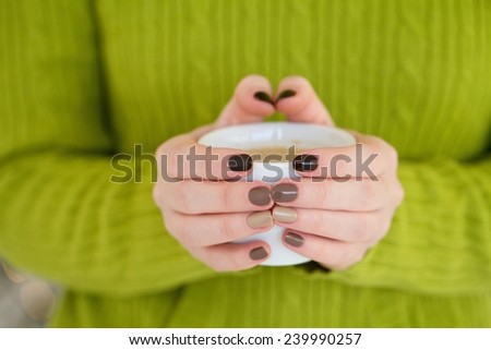 Woman holding coffee cup in christmas light background - stock photo
