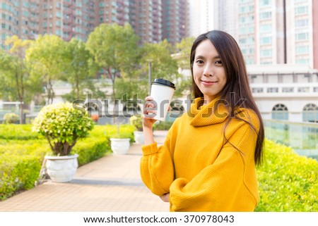 Woman holding coffee outdoors - stock photo