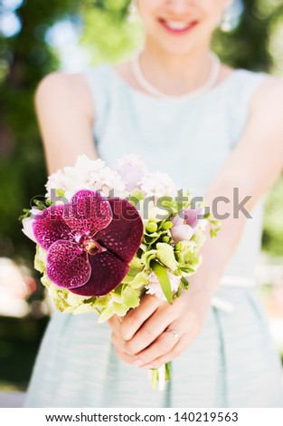 Woman holding colorful wedding bouquet with beautiful purple orchid - stock photo