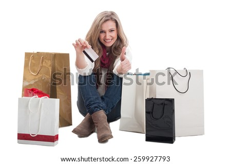 Woman holding credit card and showing thumbs up surrounded by shopping bags - stock photo