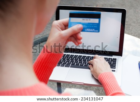 Woman holding credit card and using computer for online shopping - stock photo