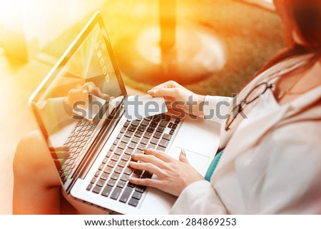 woman holding credit card on laptop for online shopping - stock photo