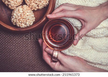 Woman holding cup of black tea on white woollens and rice crispy balls in wooden bowl close up - stock photo