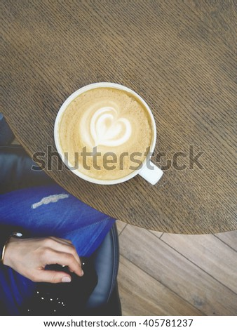 Woman holding cup of coffee latte, with heart shape.A Cup of hot latte art coffee on wooden table.Admission lunch coffee at the coffee shop. Coffe time - stock photo