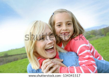 Woman holding daughter on her back - stock photo