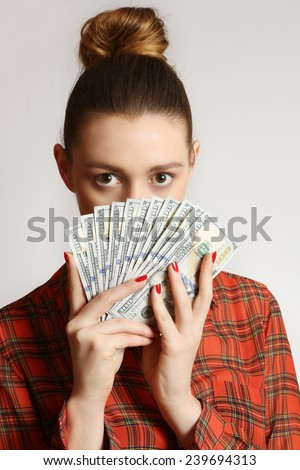 Woman holding dollar bills, Close up of young woman covering her face with bunch of dollar bills  - stock photo