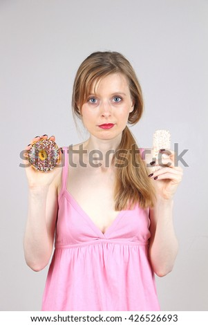 Woman holding donut and rice cake in her hands giving you a choice - stock photo