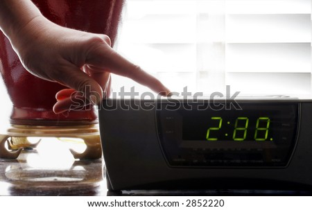 woman holding down the button of a clock radio to set the time - stock photo