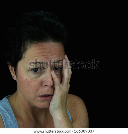 Woman holding face in emotional upset. Mental health/stress/depression. Isolated on black background. - stock photo
