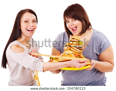 Woman holding fast food and measuring tape. Concept. - stock photo