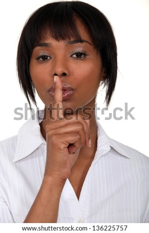 Woman holding finger to lips - stock photo