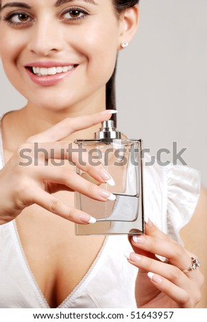woman holding glass perfume bottle - stock photo