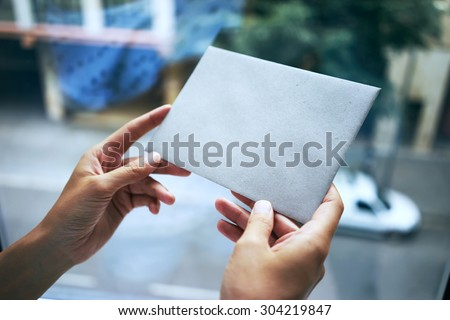 woman holding gray envelope on the city background              - stock photo