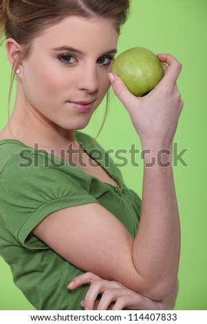 Woman holding green apple against face - stock photo