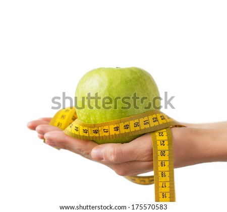 Woman holding green apple and yellow measurement tape in both hands. - stock photo