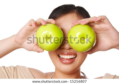 Woman holding green apple in front of her eyes - stock photo