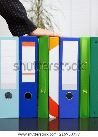 woman holding hand on binders. Care of company documentation - stock photo