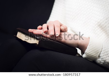 Woman holding hands over her holy bible and praying to God. - stock photo