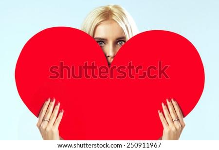 Woman holding heart symbol - stock photo