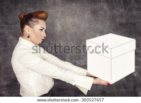 Woman holding heavy box in her hands on the blackboard background - stock photo