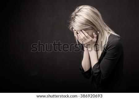 Woman holding her face in her hands  - stock photo