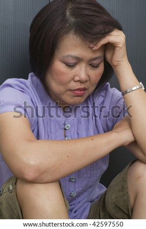 Woman holding her head and feeling depressed - stock photo