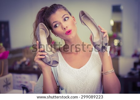 Woman holding high-heeled sandals and having fun at a shoe shop - stock photo