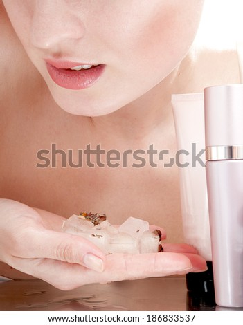 Woman holding ice cubes near face and cosmetics - isolated on white background. - stock photo