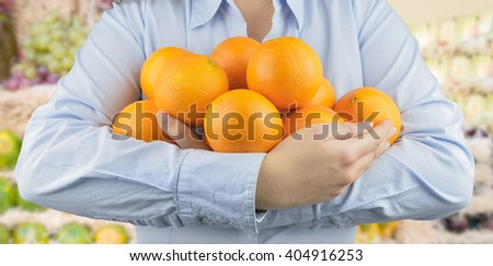 woman holding in her arms citric fruits like oranges at the greengrocer on the store background - stock photo