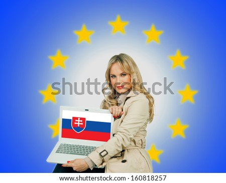 woman holding laptop with slovakia flag on the screen and european union stars in the background - stock photo