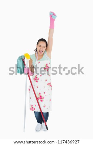 Woman holding lot of cleaning tools and a sponge in the air and shouting - stock photo