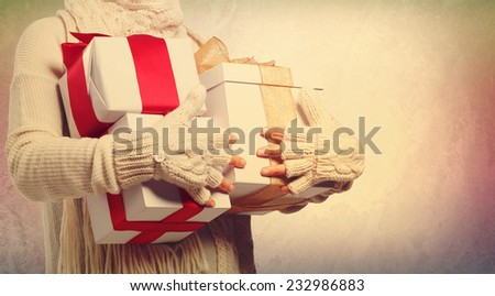 Woman holding many present boxes with red ribbon  - stock photo