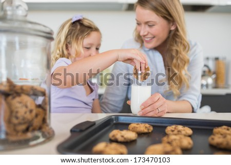 Woman holding milk glass while daughter dipping cookie in it at kitchen counter - stock photo