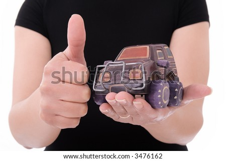 Woman holding miniaturized car in her hands over white background - stock photo
