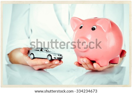 Woman holding model of car and piggy bank close up - stock photo