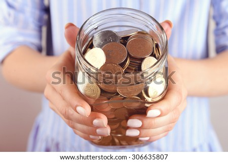 Woman holding money jar with coins close up - stock photo