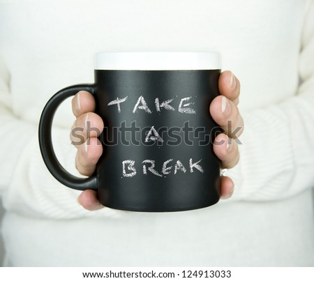 woman holding mug of drink with take a break text in chalk - stock photo
