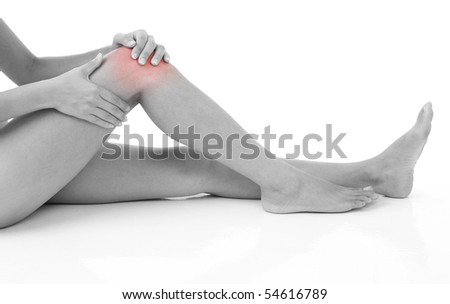 Woman holding on sore knee isolated on white. - stock photo
