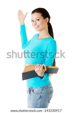 Woman holding open book and showing copyspace. - stock photo