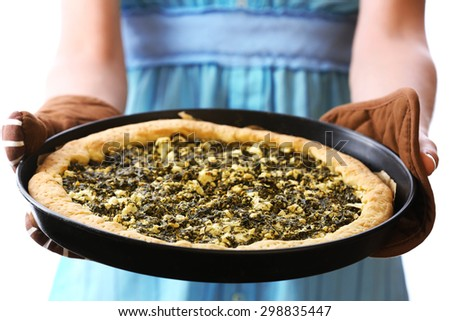 Woman holding open pie with spinach close up - stock photo
