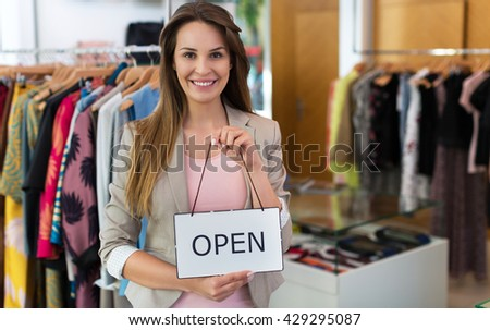 Woman holding open sign in clothes shop  - stock photo