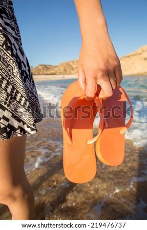 woman holding orange flops on the shoreline - stock photo