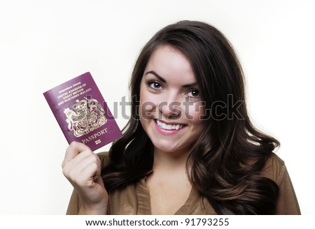 woman holding out a UK passport in her hand - stock photo