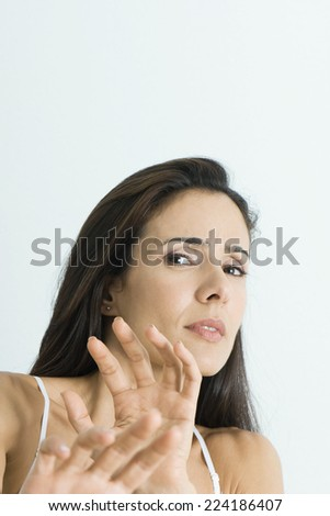 Woman holding out hands, backing away from camera, portrait - stock photo