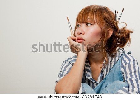 woman holding paintbrush looking pensive isolated over white background. - stock photo